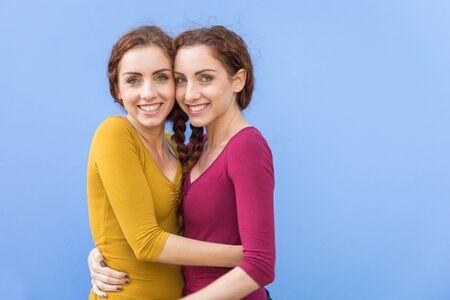 Hermosas hermanas gemelas que se unen y se divierten al aire libre