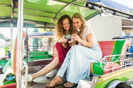 Beautiful women visiting Bangkok attractions and landmarks in Thailand - Young happy tourists exploring a south-east asian city