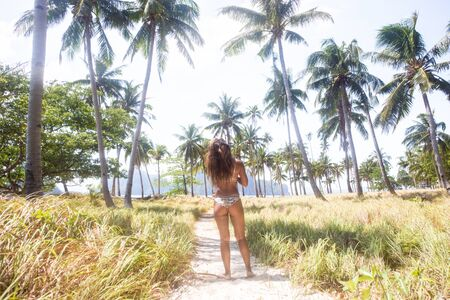 Beautiful woman on a tropical beach with blue water and palm trees - El Nido, Palawan, Philippines