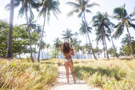 Belle femme sur une plage tropicale avec de l'eau bleue et des palmiers - El Nido, Palawan, Philippines