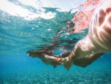 Woman swimming underwater on a tropical beach with blue water Reklamní fotografie