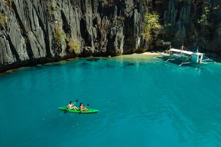Couple kayaking on a tropical beach with blue water and palm trees - El Nido, Palawan, Philippines Reklamní fotografie - 128482633