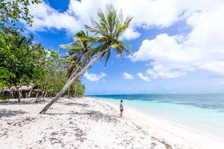Man wearing swimwear and tropical shirt on a beautiful sandy tropical beach Reklamní fotografie - 128482625