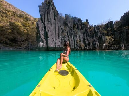 Woman kayaking on a tropical beach with blue water