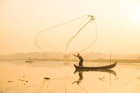 Myanmar fisherman throwing fishing net at lake near U Bein Bridge in Mandalay, Myanmar. Reklamní fotografie - 128482479
