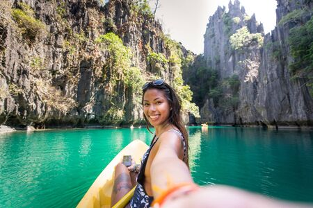 Woman kayaking in the Small Lagoon in El Nido, Palawan, Philippines Reklamní fotografie - 128482428