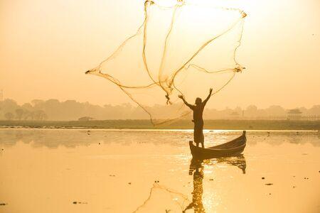 Myanmar fisherman throwing fishing net at lake near U Bein Bridge in Mandalay, Myanmar. Reklamní fotografie - 128482132