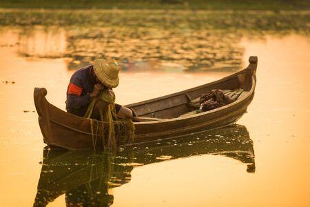 Myanmar fisherman throwing fishing net at lake near U Bein Bridge in Mandalay, Myanmar. Reklamní fotografie - 128482135