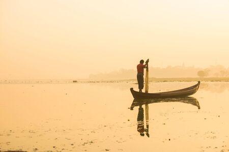 Myanmar fisherman throwing fishing net at lake near U Bein Bridge in Mandalay, Myanmar.