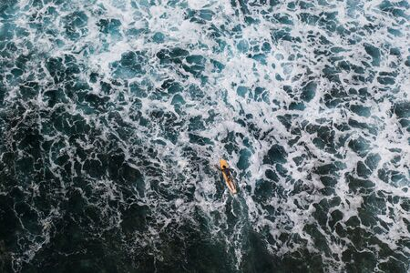 Surfer at Clpud 9 pier in Siargao, Philippines - Aerial view of surfers swimming into the ocean