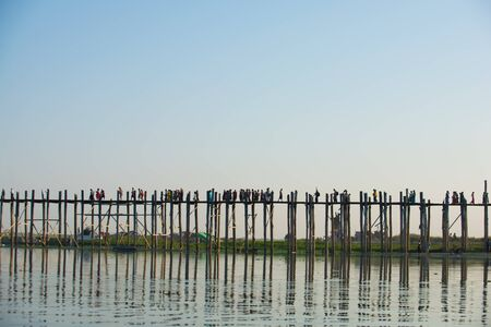 Sunset with silhouette of people walking on Bridge U-Bein in the evening, Amarapura, Mandalay, Myanmar Standard-Bild - 128454173
