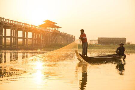 Myanmar pescatore gettando rete da pesca nel lago vicino al ponte U Bein a Mandalay, Myanmar.