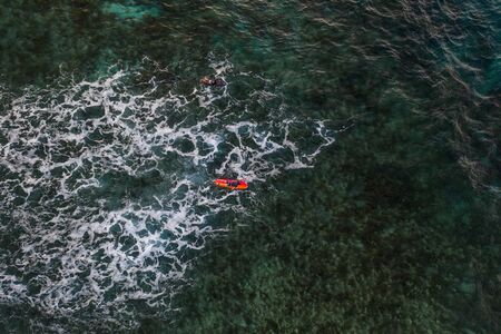 Surfer at Clpud 9 pier in Siargao, Philippines - Aerial view of surfers swimming into the ocean Stock Photo