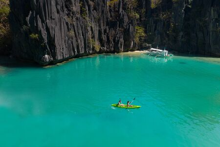 Couple kayaking on a Tropical Island with blue water