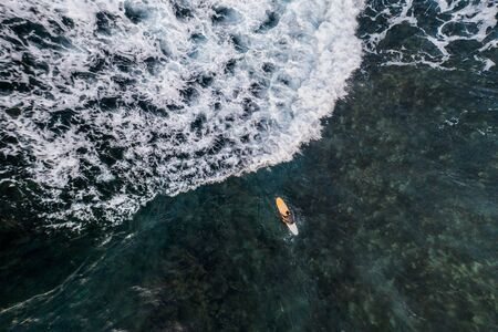Aerial view of surfers swimming into the ocean