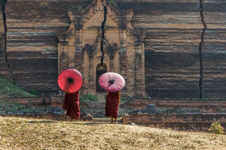 Novice buddhist monks with traditional dress at the unfinished Mingun temple, Mandalay - Myanmar Stock Photo