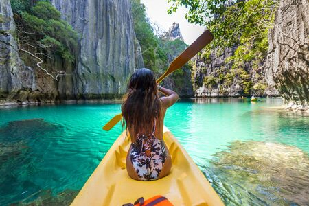 Woman kayaking in the Small Lagoon in El Nido, Palawan, Philippines 写真素材