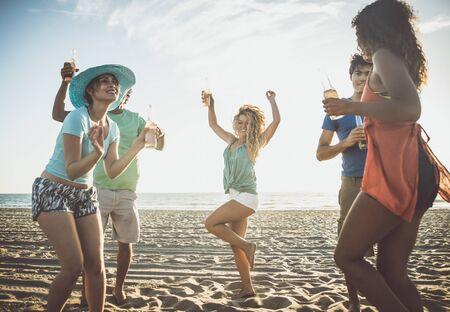 Grupo de amigos divirtiéndose en la orilla del mar Foto de archivo