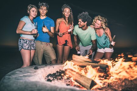 Group of friends having fun on the beach with bonfire