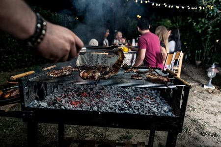 Group of friends making barbecue in the backyard at dinner time Stock fotó - 128422090