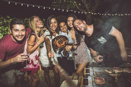 Group of friends making barbecue in the backyard at dinner time Stock fotó - 128422094