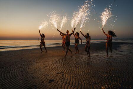 Gruppe Freunde, die Spaß haben, auf dem Strand mit Wunderkerzen zu laufen