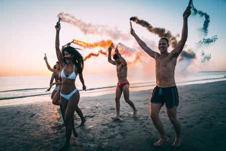 Groep vrienden die pret hebben die op het strand met rookbommen lopen
