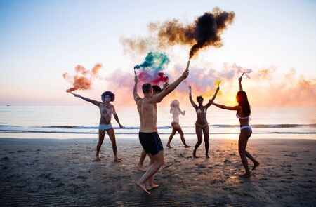 Group of friends having fun running on the beach with smoke bombs Stockfoto