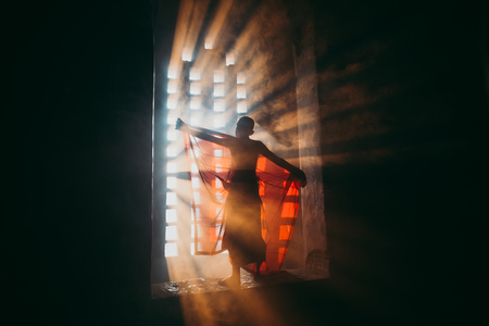 Children monk praying at the buddhist temple. artistic portrait with a monk silhouette in the mist and light filtering from a window Editorial