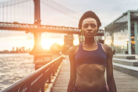 ニューヨーク市の日の出で午前中にアスリートの女性のトレーニング, 背景にブルックリン 写真素材