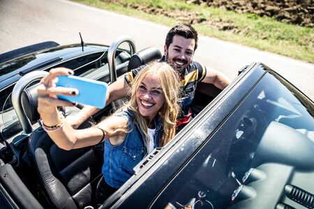 Couple driving on a convertible car and having fun Reklamní fotografie