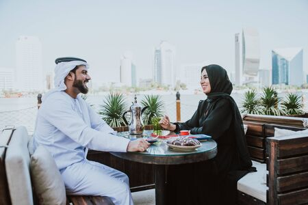 Happy couple spending time in Dubai. man and woman wearing traditional clothes having a conversation in a cafe