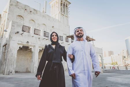 Happy couple spending time in Dubai. man and woman wearing traditional clothes making shopping in the old city
