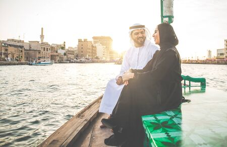 Happy couple spending time in Dubai. man and woman wearing traditional clothes taking a cruise on the river