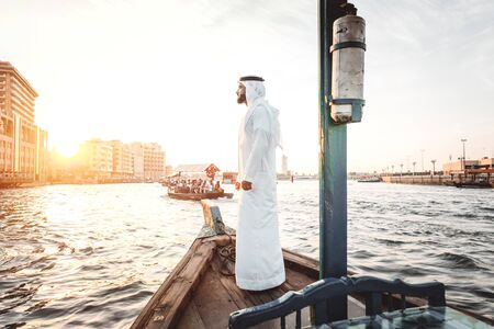 Arabic man with traditional clothes on the top of the boat, on the dubai river