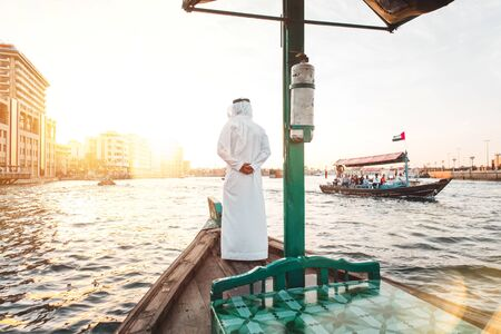 Arabic man with traditional clothes on the top of the boat, on