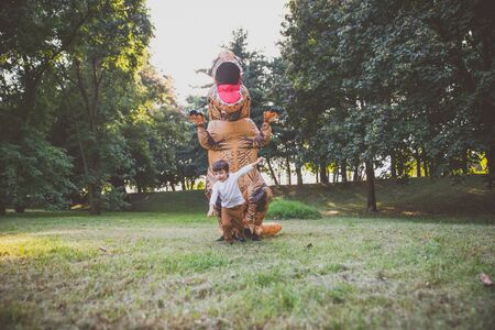 Father and son playing at the park, with a dinosaur costume, having fun with the family outdoor Stock Photo - 128953493
