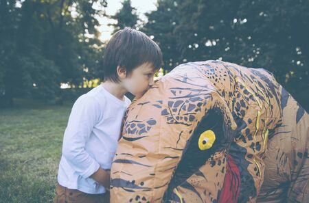 Father and son playing at the park, with a dinosaur costume, having fun with the family outdoor
