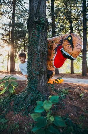 Father and son playing at the park, with a dinosaur costume, having fun with the family outdoor Stock Photo - 128953567