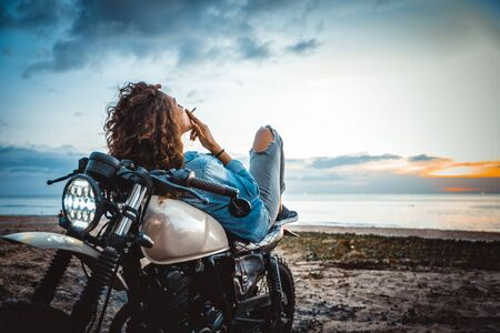 Beautiful girl having fun driving her custom cafe racer motorcycle, enjoying the sunset on the beach 스톡 콘텐츠 - 128955590