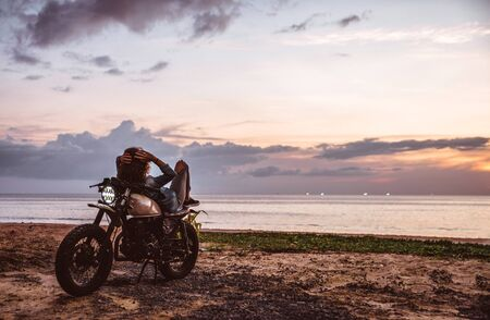 Beautiful girl having fun driving her custom cafe racer motorcycle, enjoying the sunset on the beach