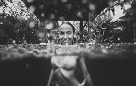 Beautiful woman having a bath in the swimming pool while it s raining Stock fotó