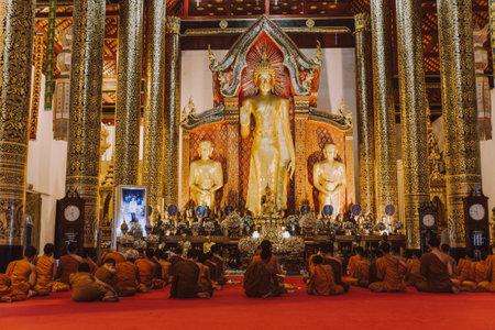 Wat chedi luang, monks praying inside a temple