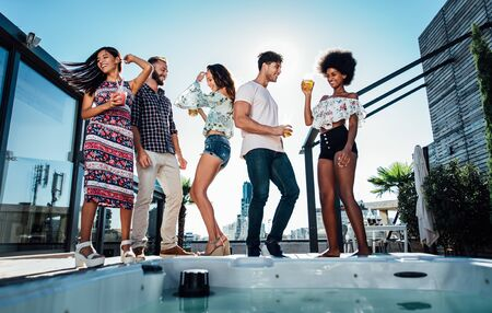 Group of friends having fun on the rooftop of a beautiful penthouse Stok Fotoğraf