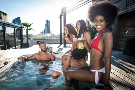 Group of friends having fun on the rooftop of a beautiful penthouse Banco de Imagens