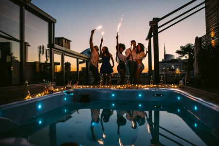 Group of friends having fun on the rooftop of a beautiful penthouse Фото со стока