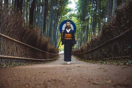 Beautiful japanese senior woman walking in the bamboo forest