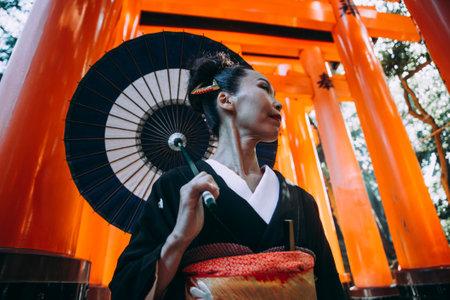 Beautiful japanese senior woman walking in the fushimi inari shrine in Kyoto