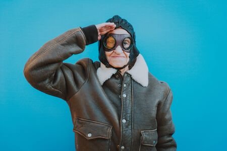 Funny portraits with old grandmother. Senior woman acting as an aviator from the first world war.