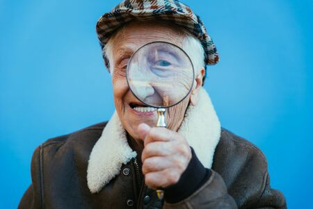 Funny portraits with old grandmother. Senior woman acting as an investigator with the magnifying lense Stock Photo